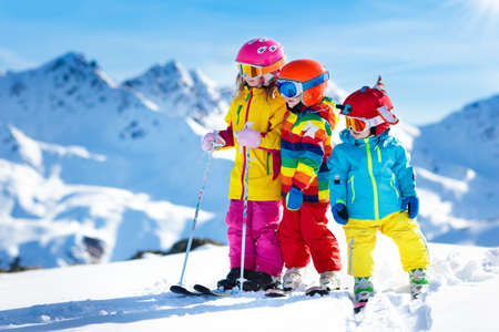 Foto de Child skiing in the mountains. Kid in ski school. Winter sport for kids. Family Christmas vacation in the Alps. Children learn downhill skiing. Alpine ski lesson for boy and girl. Outdoor snow fun. - Imagen libre de derechos