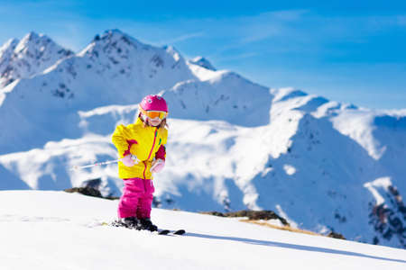 Foto de Child skiing in mountains. Active toddler kid with safety helmet, goggles and poles. Ski race for young children. Winter sport for family. Kids ski lesson in alpine school. Little skier racing in snow - Imagen libre de derechos