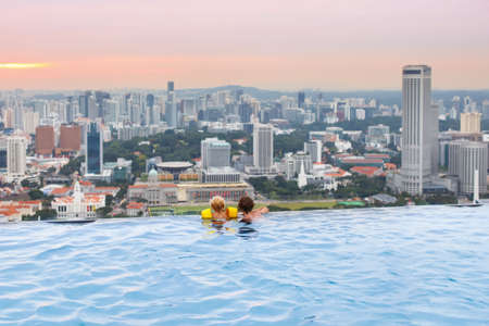 Photo pour Children swimming in roof top outdoor pool on family vacation in Singapore. City skyline from infinity pool in luxury hotel. Kids swim and enjoy skyscraper view in Asia. Travel with young child. - image libre de droit