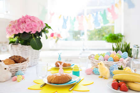 Foto de Easter breakfast table setting. Decoration for Easter family celebration. Eggs basket and spring flowers. Bread, croissant and fruit for kids meal. Egg and pastel bunny decor in kitchen at window. - Imagen libre de derechos