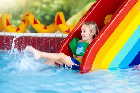 Photo pour Child on swimming pool slide. Kid having fun sliding in water amusement park. Kids swim. Family summer vacation in tropical resort. Little boy in baby pool with colorful rainbow water slide. - image libre de droit