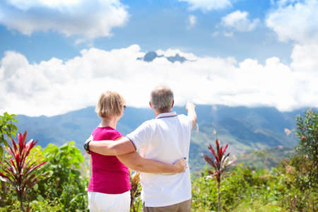 Foto de Senior couple hiking in mountains. Mature man and woman trekking in Borneo jungle. Family looking at Mount Kinabalu peak, highest mountain of Malaysia. Summer vacation in Southeast Asia. - Imagen libre de derechos