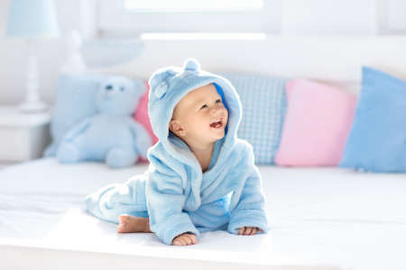 Photo pour Cute happy laughing baby boy in soft bathrobe after bath playing on white bed with blue and pink pillows in sunny kids room. Child in clean and dry towel. Wash, infant hygiene, health and skin care. - image libre de droit