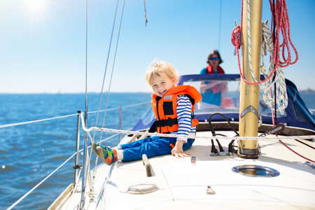 Photo pour Kids sail on yacht in sea. Child sailing on boat. Little boy in safe life jackets travel on ocean ship. Children enjoy yachting cruise. Summer vacation for family. Young sailor on sailboat front deck. - image libre de droit