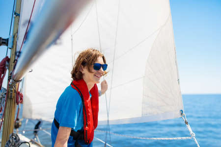 Photo pour Teen age boy learning to sail on yacht in the sea. Young man sailing on boat. Sailor in safe life jacket. Teenager on yachting cruise. Summer vacation. Kid on sailboat. - image libre de droit