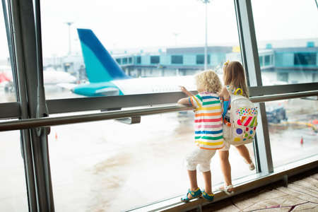 Photo for Kids at airport. Children look at airplane. Traveling and flying with child. Family at departure gate. Vacation and travel with young kid. Boy and baby before flight in terminal. Kids fly a plane. - Royalty Free Image