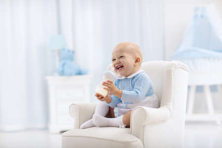 Foto de Adorable baby boy playing on a blue floor mat and drinking milk from a bottle in a white sunny nursery with rocking chair and bassinet. Bedroom interior with infant crib. Formula drink for infant. - Imagen libre de derechos