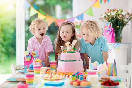 Foto de Kids birthday party. Children blow out candles on pink bunny cake. Pastel rainbow decoration and table setting for kids event, banner and flag. - Imagen libre de derechos
