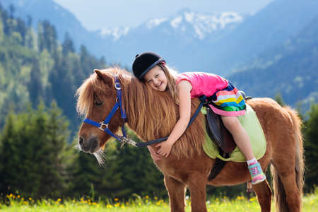 Photo pour Kids riding pony in the Alps mountains. Family spring vacation on horse ranch in Austria, Tirol. - image libre de droit
