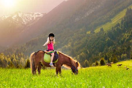 Photo pour Kid riding pony in the Alps mountains. - image libre de droit