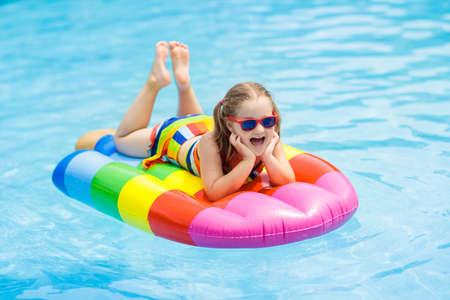 Foto de Happy child on inflatable ice cream float in outdoor swimming pool of tropical resort. - Imagen libre de derechos