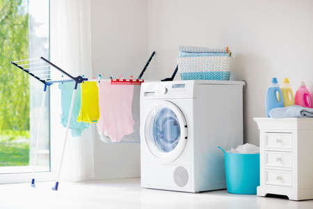 Photo pour Laundry room with washing machine or tumble dryer. Modern household devices in white sunny home. Clean washed clothes on drying rack. Liquid washing detergent in plastic bottle and fabric softener. - image libre de droit