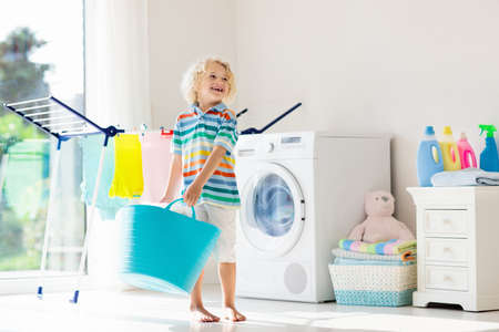 Foto de Child in a laundry room with washing machine or tumble dryer. Kid helping with family chores. Modern household devices and washing detergent in white sunny home. Clean washed clothes on drying rack. - Imagen libre de derechos
