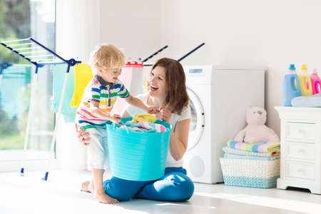 Photo pour Mother and kids in the laundry room with washing machine or tumble dryer. Family chores. Modern household devices and washing detergent in white sunny home. Clean washed clothes on drying rack. - image libre de droit