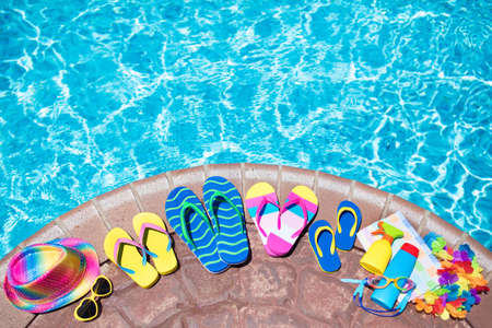 Photo pour Swimming pool accessories flat lay. Top view of beach items on pool deck. Flip flops, bikini and hat, sun glasses. Water toys. Summer vacation in tropical resort. Copy space. Colorful beach wear. - image libre de droit