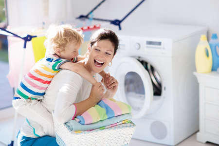 Foto für Mother and kids in the laundry room with washing machine or tumble dryer. Family chores. Modern household devices and washing detergent in white sunny home. Clean washed clothes on drying rack. - Lizenzfreies Bild