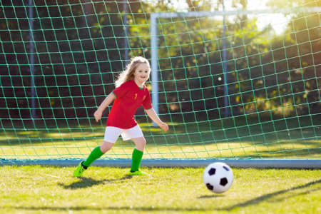 Foto de Kids play football on outdoor field. Portugal team fans. Children score a goal at soccer game. Little girl in Portuguese jersey and cleats kicking ball. Football pitch. Sports training for player. - Imagen libre de derechos