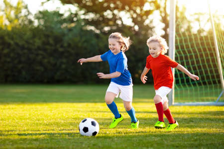 Foto de Kids play football on outdoor field. Children score a goal at soccer game. Girl and boy kicking ball. Running child in team jersey and cleats. School football club. Sports training for young player. - Imagen libre de derechos