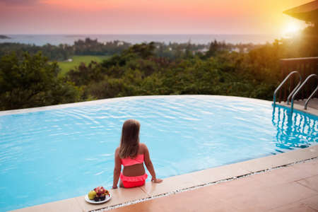 Photo pour Child at swimming pool. Little girl looking at the ocean at infinity pool of tropical resort in Asia. Luxury summer vacation with kids. Family holiday. - image libre de droit