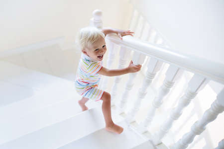 Foto de Kid walking stairs in white house. Baby boy playing in sunny staircase. Family moving into new home. Child crawling steps of modern stairway. Foyer and living room interior. Home safety for toddler. - Imagen libre de derechos