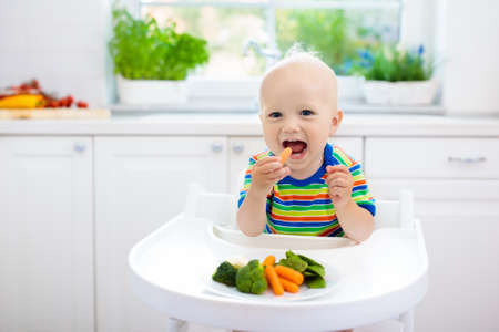 Photo pour Cute baby eating vegetables in white kitchen. Infant weaning. Little boy trying solid food, organic broccoli, cauliflower, carrot and green peas. Healthy nutrition for kids. Child biting carrot. - image libre de droit
