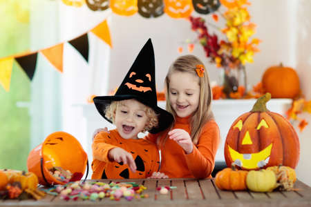 Foto de Little girl and boy in witch costume on Halloween trick or treat. Kids holding candy in pumpkin lantern bucket. Children celebrate Halloween at decorated fireplace. Family trick or treating. - Imagen libre de derechos