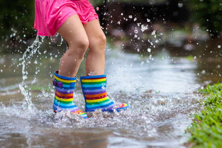 Photo pour Kid playing out in the rain. Children with umbrella and rain boots play outdoors in heavy rain. Little girl jumping in muddy puddle. Kids fun by rainy autumn weather. Child running in tropical storm. - image libre de droit