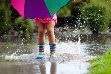 Foto de Kid playing out in the rain. Children with umbrella and rain boots play outdoors in heavy rain. Little girl jumping in muddy puddle. Kids fun by rainy autumn weather. Child running in tropical storm. - Imagen libre de derechos