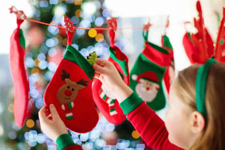 Photo pour Kids opening Christmas presents. Child searching for candy and gifts in advent calendar on winter morning. Decorated Christmas tree for family with children. Little girl in Xmas pajamas. - image libre de droit