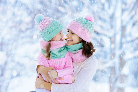 Photo pour Mother and child in knitted winter hats play in snow on family Christmas vacation. Handmade wool hat and scarf for mom and kid. Knitting for kids. Knit outerwear. Woman and little girl in snowy park. - image libre de droit