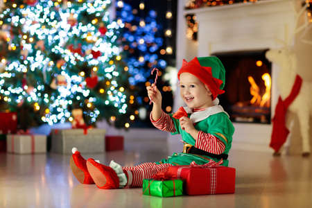 Photo for Child opening present at Christmas tree at home. Kid in elf costume with Xmas gifts and toys. Little baby boy with gift box and candy at fireplace. Family celebrating winter holidays. Home decoration. - Royalty Free Image
