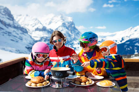 Photo pour Family with children enjoying apres ski lunch with traditional Swiss raclette and cheese fondue in restaurant on top of snow covered mountain on winter or Christmas vacation. Parents and kids skiing. - image libre de droit