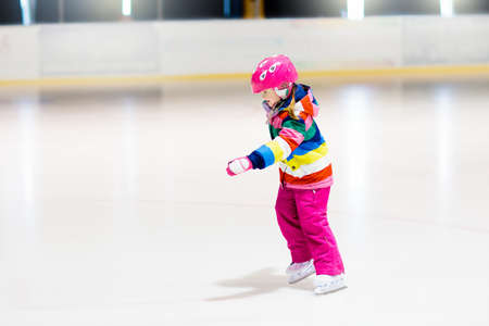 Photo for Child skating on indoor ice rink. Kids skate. Active family sport during winter vacation and cold season. Little girl in colorful wear training or learning ice skating. School sport activity and clubs - Royalty Free Image