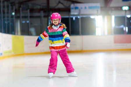 Foto de Child skating on indoor ice rink. Kids skate. Active family sport during winter vacation and cold season. Little girl in colorful wear training or learning ice skating. School sport activity and clubs - Imagen libre de derechos