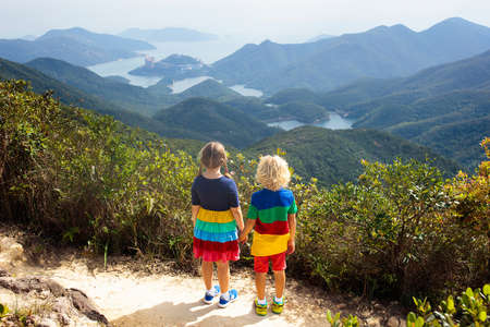 Photo pour Family with kids hiking in Hong Kong mountains. Beautiful landscape with hills, sea and city skyscrapers in Hong Kong, China. Outdoor activity in the nature for parents and children. - image libre de droit