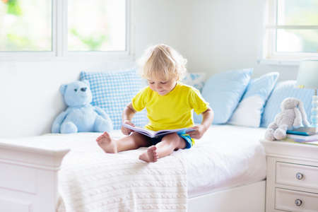 Photo pour Child playing in bed in white sunny bedroom with window. Kids room and interior design. Baby boy at home. Bedding and textile for children nursery. Kid with toy and book. Nap and sleep time. - image libre de droit