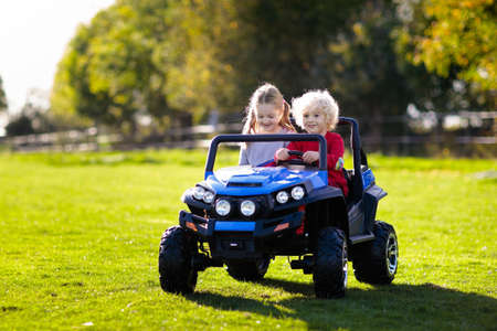 Foto de Kids driving electric toy car in summer park. Outdoor toys. Children in battery power vehicle. Little boy and girl riding toy truck in the garden. Family playing in the backyard. - Imagen libre de derechos