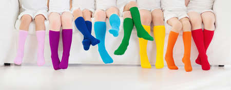 Foto de Kids wearing colorful rainbow socks. Children footwear collection. Variety of knitted knee high socks and tights. Child clothing and apparel. Kid fashion. Legs and feet of little boy and girl group. - Imagen libre de derechos