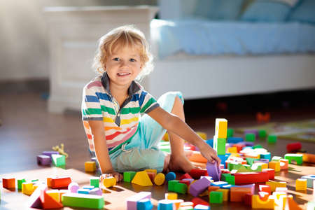 Foto de Child playing with colorful toy blocks. Kids play. Little boy building tower of block toys sitting on dark floor in sunny white bedroom. Educational game for baby and toddler. Children build toy house - Imagen libre de derechos