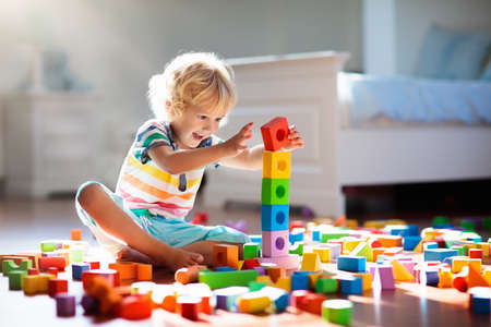 Photo for Child playing with colorful toy blocks. Kids play. Little boy building tower of block toys sitting on dark floor in sunny white bedroom. Educational game for baby and toddler. Children build toy house - Royalty Free Image