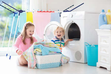 Foto de Children in the laundry room with washing machine or tumble dryer. Kids help with family chores. Modern household devices and washing detergent in white sunny home. Clean washed clothes on drying rack. - Imagen libre de derechos