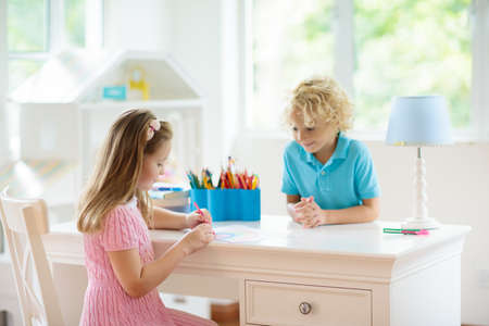 Foto de Child drawing rainbow. Kid painting at home. Little girl and boy doing homework after school. Kids desk with abacus in white sunny bedroom. Children study, learn to read and write. Bedroom for student - Imagen libre de derechos