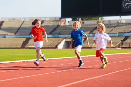 Photo pour Child running in stadium. Kids run on outdoor track. Healthy sport activity for children. Little girl at athletics competition race. Young athlete in training. Runner exercising. Jogging for kid. - image libre de droit