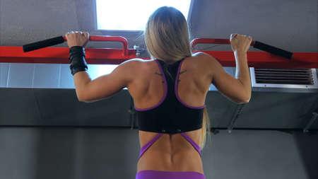 Foto de Blonde woman doing pull ups at the gym. Back view. - Imagen libre de derechos