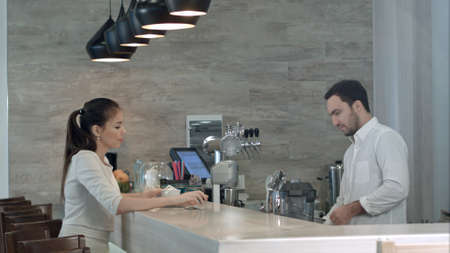 Photo for Young woman asking male barista for a bill and paying while sitting at cafe counter - Royalty Free Image