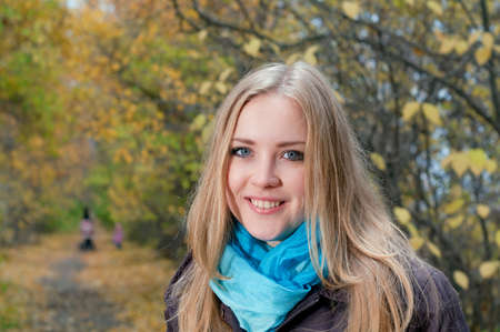 Young pretty blonde woman in the autumn park