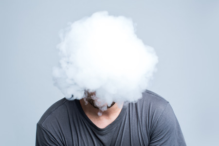 Foto de Face covered with thick white smoke isolated on light  - Imagen libre de derechos