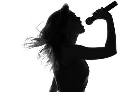 Photo pour silhouette of a woman singing with a microphone in hands - image libre de droit