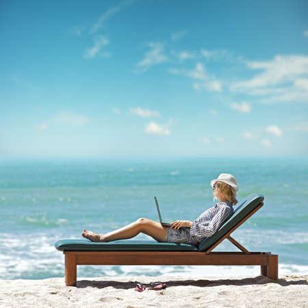 Foto de Young woman with laptop at the beach - Imagen libre de derechos