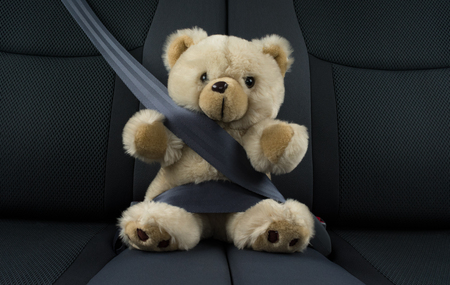 Photo pour Teddy bear is sitting in a car fastened with a seat belt, represents a child safety in a car - image libre de droit